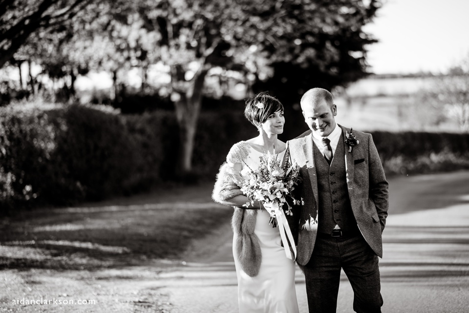 a photo of a bride and groom in a country lane
